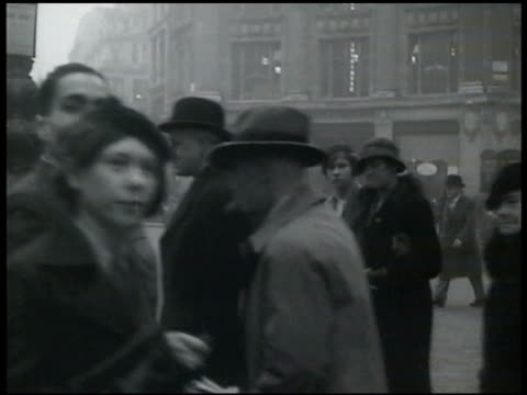 stockvideo's en b-roll-footage met women waiting to cross busy double-decker bus london street, group of pedestrians, leslie hore-belisha lighting cigarette, people crossing street w/... - 1935