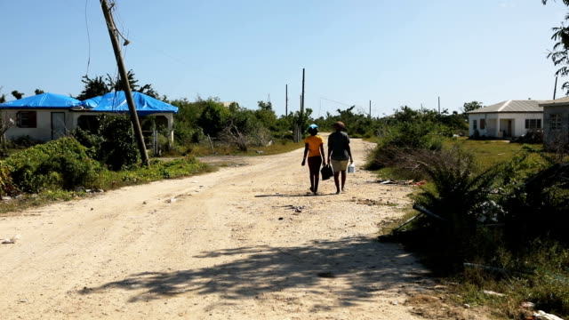 Women walk along a street on the nearly destroyed island of Barbuda on December 8 2017 in Cordington Barbuda Barbuda which covers only 62 square...