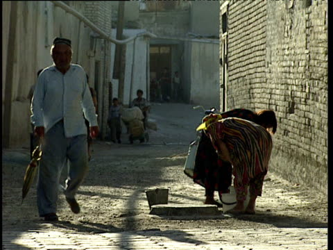 women walk away from drainage manhole carrying water buckets bukhara uzbekistan - ムラがある点の映像素材/bロール