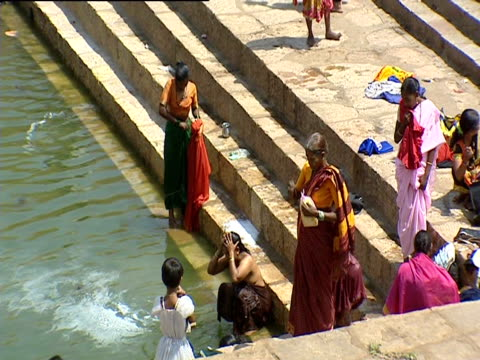 Women walk down steps to bathe in India