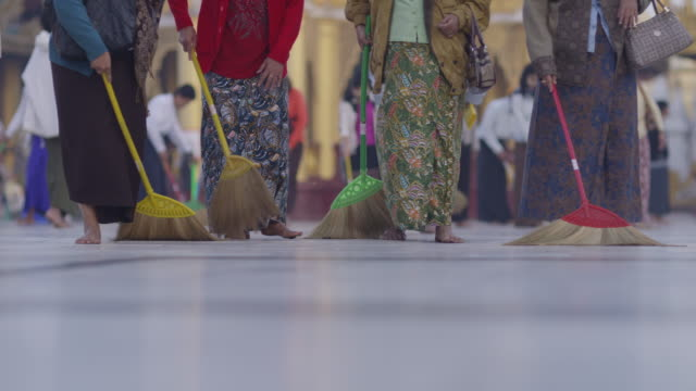 Women walk in line sweeping a temple square