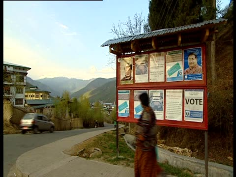 women walk past a notice board featuring political advertisements - notice board stock videos and b-roll footage
