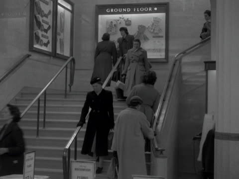 vidéos et rushes de women walk up and down a staircase in a department store 1957 - store