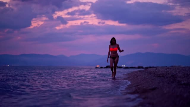 vídeos de stock e filmes b-roll de women walking along a beach at dusk - swimwear
