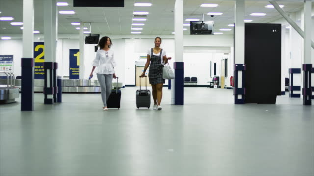women walking at airport - wheeled luggage stock videos and b-roll footage