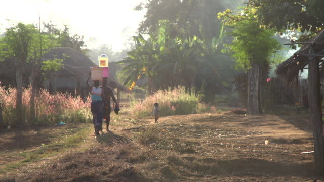 Women walking down a dusty dirt road in African village