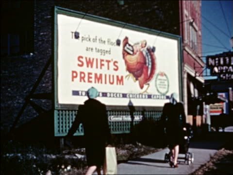 vidéos et rushes de 1941 women walking in front of swift's premium billboard / chicago / industrial - prelinger archive