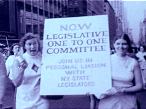 vidéos et rushes de vs women walking in peaceful protest women's liberation demonstration w/ banners signs babies in new york city street new york radical feminist now... - 1976