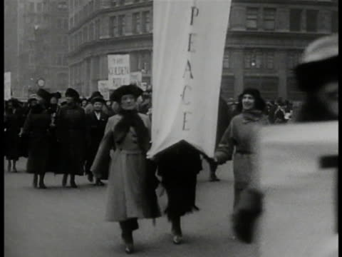 women walking in street parade w/ banners 'golden rule', 'peace', woman w/ 'no more war' flyers. women w/ 'women of the world unite to save life'... - parade stock videos & royalty-free footage