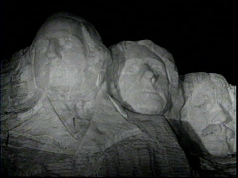 women walking near display of large spotlights / montage of mount rushmore at night with spotlights on faces / closer view of the monument's faces / - bergsvägg bildbanksvideor och videomaterial från bakom kulisserna