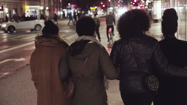 women walking on city street at night on the way to party - holding hands stock videos & royalty-free footage