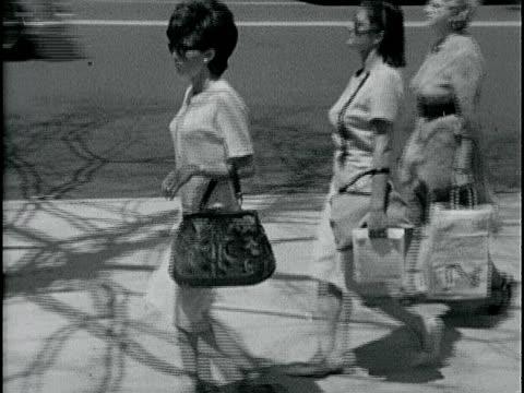 vídeos de stock, filmes e b-roll de women walking on sidewalk tracking one brunette woman walking in two piece conservative dress tapestry handbag high heels people walking crossing... - 1963