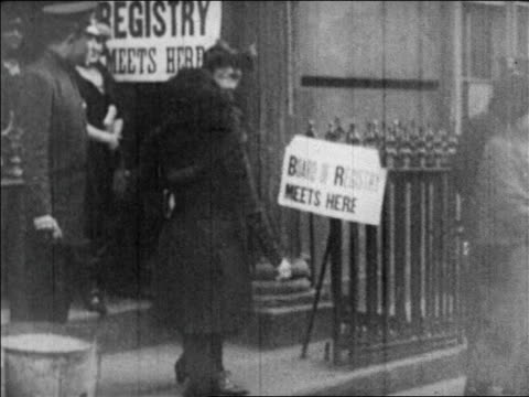 B/W 1920 women walking out of building after registering to vote / newsreel