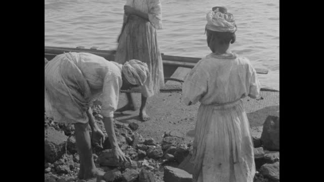 vidéos et rushes de women walking out of fenced area as other women walking into area carrying trays with piles of coal on their heads / women picking up coal lumps... - antilles occidentales