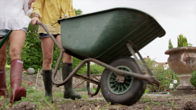 women walking with wheelbarrow - wheelbarrow stock videos and b-roll footage