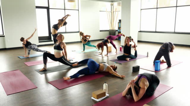 ws women warming up before hot yoga class in exercise studio - warming up stock videos & royalty-free footage