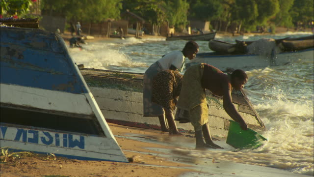 women wash clothes on the shoreline of lake malawi - only mid adult women stock videos & royalty-free footage