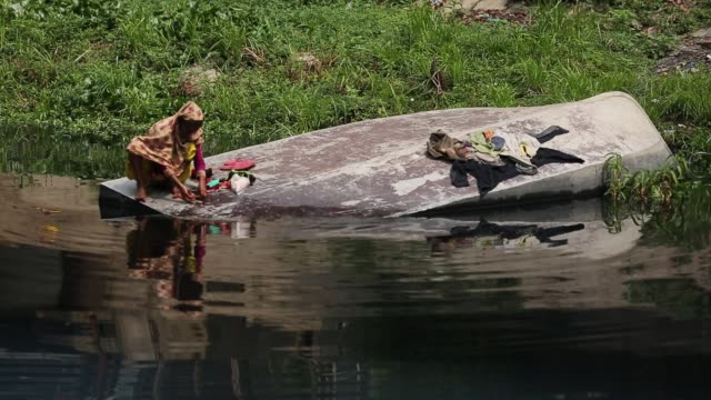 a women wash cloths in polluted water from buriganga river in dhaka bangladesh the chemical waste of mills and factories household waste eventually... - world water day stock videos and b-roll footage