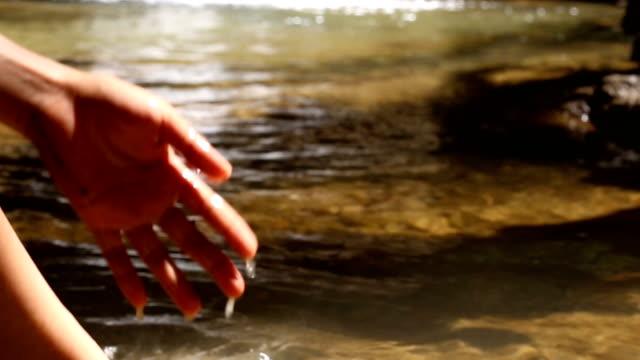 frauen waschen hand am wasserfall, entspannung am wasserfall im urlaub. - schöne natur stock-videos und b-roll-filmmaterial