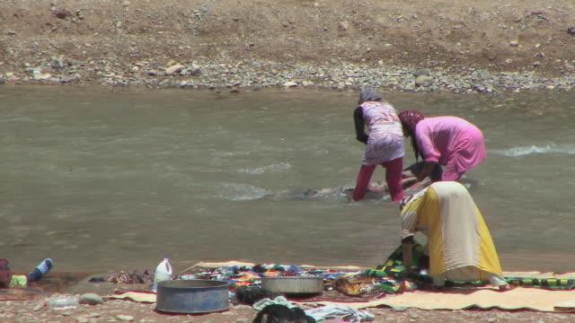 vídeos y material grabado en eventos de stock de ws women washing rugs in dades river, el kaala mgouna, morocco - hacer la colada