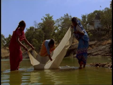 ms women washing sheet in lake, bandhavgarh national park, india - hygiene stock videos & royalty-free footage