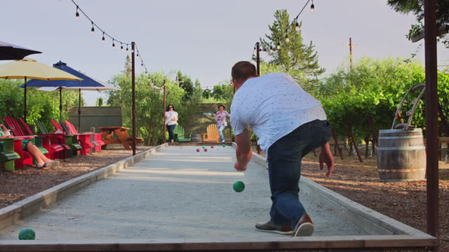 women watching many playing bocce ball in vineyard - slow motion - bowling ball stock videos & royalty-free footage