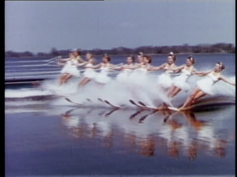 1957 FILM MONTAGE WS Women water skiing and holding red banners that spell out Cypress Gardens/ WS Women in white bathing suits waterskiing in a row/ Cypress Gardens, Florida