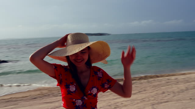 Women wear a sea hat and she is happy on the beach seaside, cloud and blue sky is endless background.