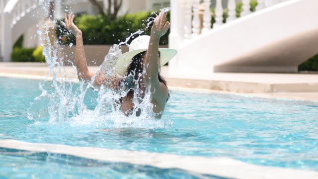 vídeos de stock, filmes e b-roll de as mulheres usam biquínis para nadar e beber cocktails no verão quente na piscina. - acampamento de férias