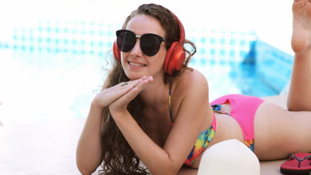 kvinnor bär bikinis läs böcker och lyssna på musik på sommaren rekreation pool. - utebassäng bildbanksvideor och videomaterial från bakom kulisserna