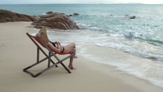 Women wear hat Sitting she is happy on comfortable chair on the beach seaside, cloud and blue sky is endless background