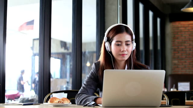 women wear white headphones, watch movies and listen to music - stereo personale video stock e b–roll