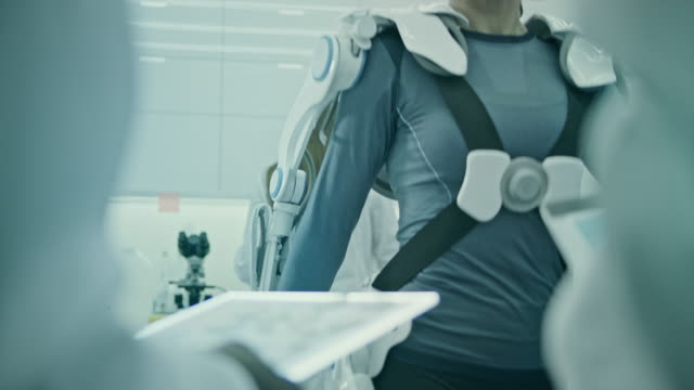 women wearing and testing exo suits in laboratory. - exoskeleton stock videos & royalty-free footage