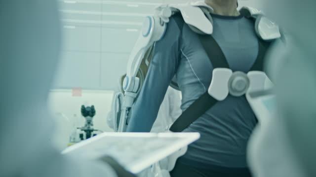 vidéos et rushes de femmes portant et testant des costumes exo dans le laboratoire. - agence de design