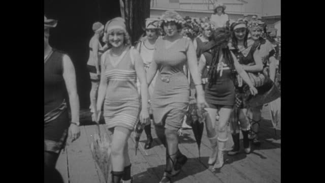vídeos de stock, filmes e b-roll de women wearing bathing suits approach camera as they walk in line outdoors during beauty pageant or parade / note: exact year not known - swimwear
