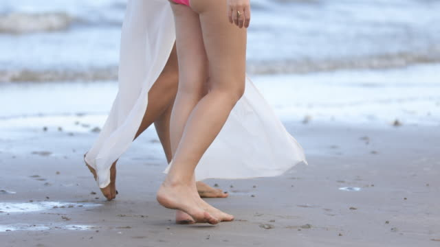 women wearing bikinis are walking with friends at the beach in summer. - bikini stock videos & royalty-free footage