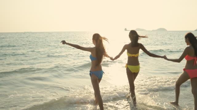 明るい晴れた朝と海とビーチに走って明るい色のビキニを着ている女性。 - 水着点の映像素材/bロール