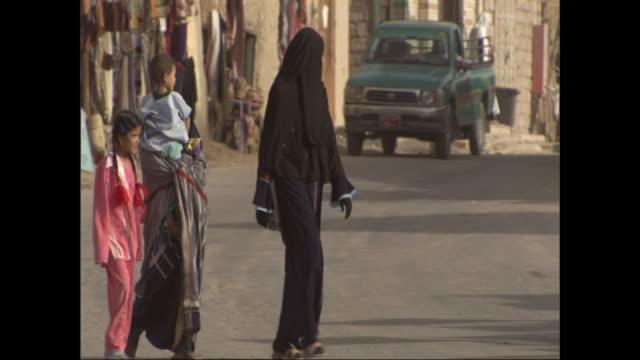 women wearing burkas cross a busy street in egypt. - モデスト・ファッション点の映像素材/bロール