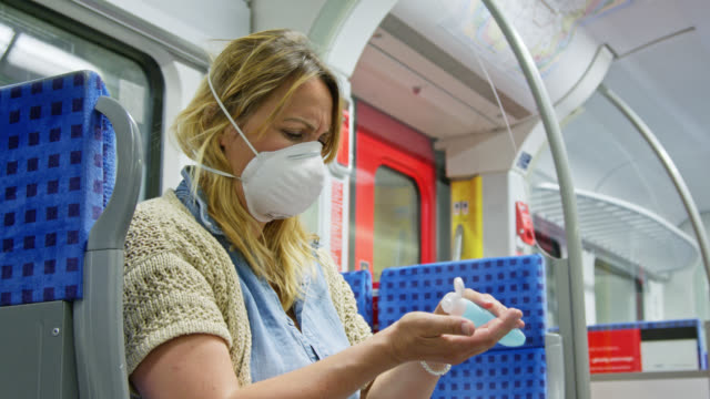 women wearing ffp-2 protective mask enters metro train sits down and uses hand sanitiser desinfectant for disinfection of her hands. - regeln stock-videos und b-roll-filmmaterial