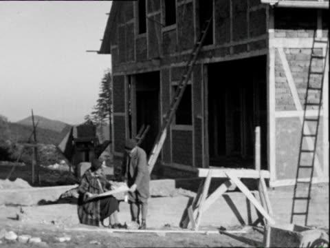 vídeos y material grabado en eventos de stock de 1938 b/w montage women wearing fur coat sitting in sun while holiday home being constructed / thuringia, germany  - accesorio de cabeza
