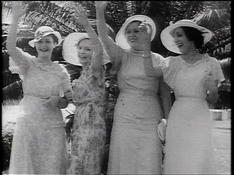 b/w 1934 4 women wearing hats + dresses waving goodbye to offscreen ship - prelinger archive stock-videos und b-roll-filmmaterial