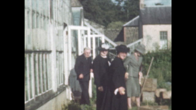 women wearing hats walking in garden outside greenhouse as man walks out of the greenhouse to join them home movie shot at a house near muckamore co... - outdoors stock videos & royalty-free footage