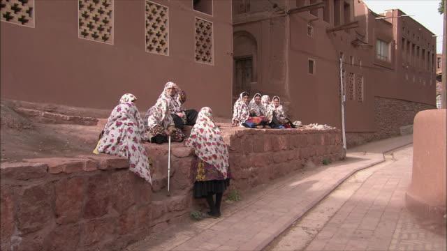 ws women wearing headscarves gathered outside house, abyaneh, iran - 中東点の映像素材/bロール