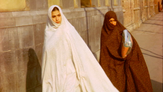 stockvideo's en b-roll-footage met women wearing hijab at street on may 01 1960 in tehran iran - hoofddoek