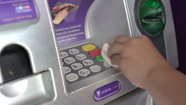 vidéos et rushes de femmes utilisant le gant en plastique avant d'employer la machine de distributeur automatique de billets - invisible