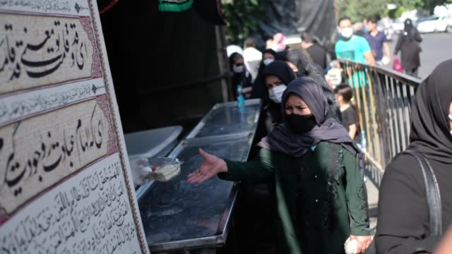 women wearing protective face masks receive donated meal as they attend a religious ceremony to commemorate tasoua a day ahead of ashura in southern... - ashura muharram stock videos & royalty-free footage