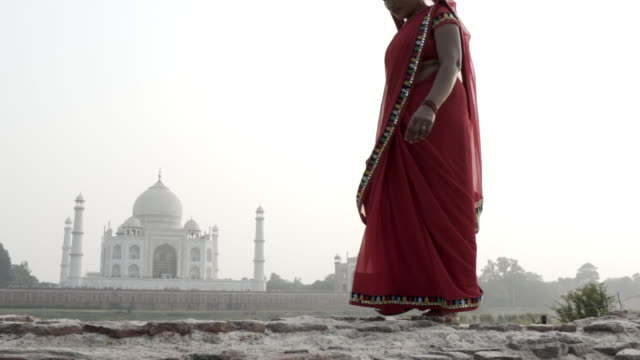women wearing saris, walking past taj mahal. india. - taj mahal stock videos and b-roll footage