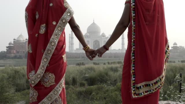 Women wearing saris, walking past Taj Mahal. India.