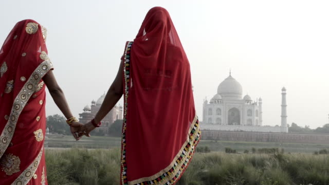 Women wearing saris, walking past Taj Mahal. India.
