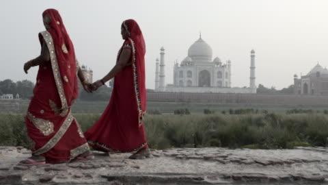 stockvideo's en b-roll-footage met women wearing saris, walking past taj mahal. india. - unesco world heritage site